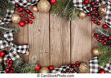 Christmas frame with white and black checked buffalo plaid ribbon, baubles and branches, top view on a wood background