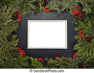 Christmas framework with evergreen fir tree, cones,holly berry and frame for photo or text.