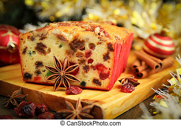 Traditional fruit cake for christmas with anise, cinnamon and dried cranberries with christmas background