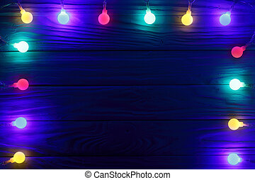 christmas garland lights on dark wooden background with copy space for your text. Top view