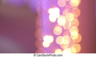 Christmas garland with Golden and purple lights, close-up. Bokeh.