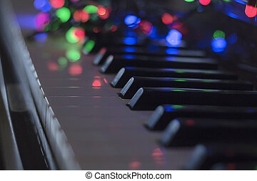 Christmas garland with lights on an electronic piano - decoration for the celebration of Christmas and New Year