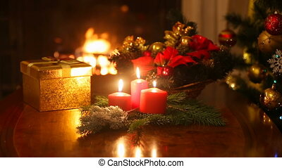 Christmas gift box and burning candles in front of burning fireplace at house