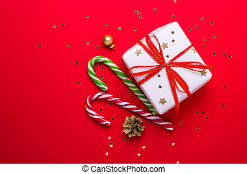 Christmas gift box and candy cane on red background
