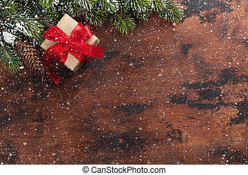 Christmas gift box and fir tree branch covered by snow on wooden background. Top view xmas backdrop with space for your greetings