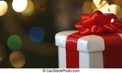 Christmas gift box on multi colored christmas tree lights background