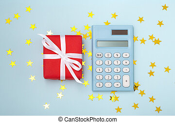 Christmas gift box with calculator on blue background, christmas budget concept