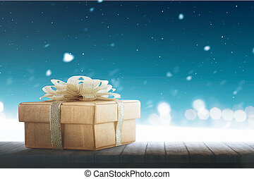 Christmas gift box with gold ribbon on wooden table
