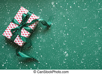 Christmas gift box with green ribbon on green surface. Space for wishes. Holiday card.