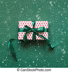 Christmas gift box with green ribbon on green surface. Xmas card. Top view. Boxing day.