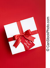 Christmas gift box with red ribbon and a bow from secret Santa on the red background