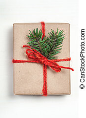Christmas gift box with xmas decorations as greeting card. Festive boxes of Christmas present with ribbon bow and fir tree branch on white background