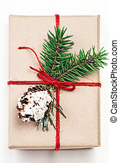 Christmas gift box with xmas decorations, Craft paper package. Greeting card wiyh Christmas present, red ribbon bow and fir tree branch on white background.