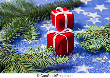 Christmas gift boxes and fir branches on a blue star background, the concept of the New Year celebration