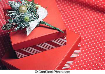 Christmas gift boxes and twig of Christmas tree on a red wrapping paper