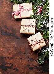 Christmas gift boxes and fir tree branch covered by snow on wooden background. Top view xmas backdrop with space for your greetings