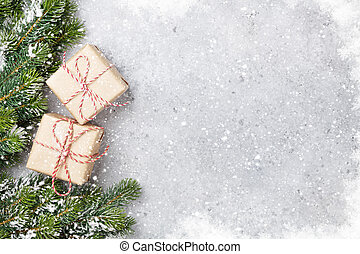 Christmas gift boxes and fir tree branch covered by snow on stone background. Top view xmas backdrop with space for your greetings