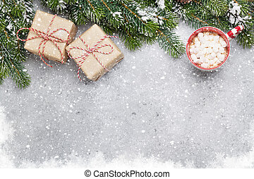 Christmas gift boxes, hot chocolate with marshmallow and fir tree branch covered by snow on stone background. Top view xmas backdrop with space for your greetings