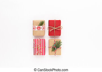 Christmas gift boxes. Composition with craft wrapped different red gifts, fir tree branch on white background.