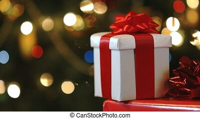 Christmas gift boxes on multi colored christmas tree lights background