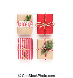 Christmas gift boxes. Square composition with craft wrapped different red gifts, fir tree branch on white background.