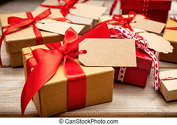 Christmas gift boxes with blank tags on wooden background