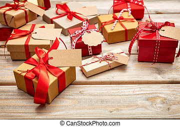 Christmas gift boxes with blank tags on wooden background, copy space
