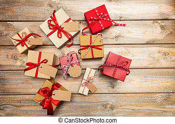 Christmas gift boxes with blank tags on wooden background, copy space, top view