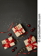Christmas gift boxes with red bow on dark background with sparkles. Holiday banner for website. Flat lay style composition, top view. Birthday or party greeting card with copy space, hen party invite