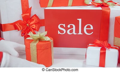 Christmas gift boxes with word Sale female hands holding...