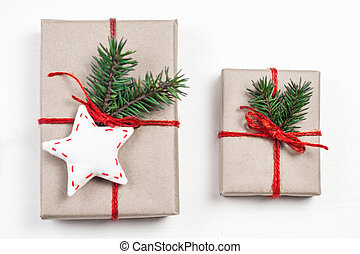 Christmas gift boxes with xmas decorations. Greeting card wiyh Christmas present, red ribbon bow and fir tree branch on white background. Craft paper package