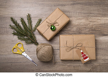 Christmas gift boxes wrapped in kraft paper, with blank gift tag on old wooden background.