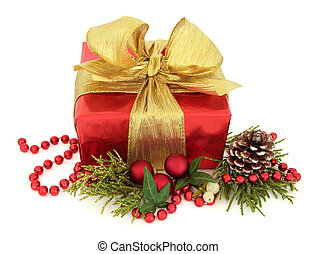 Christmas gift box in red with gold bow, bead chain and bauble cluster with glitter fauna, pine cone and ivy leaf sprig over white background.