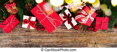 Christmas gift giving concept - christmas presents in red and white boxes on wooden table, flat lay with copy space banner