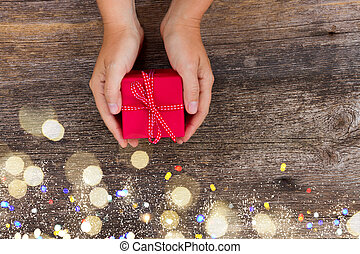Christmas gift giving - someones hand holding red box with present with bokeh lights