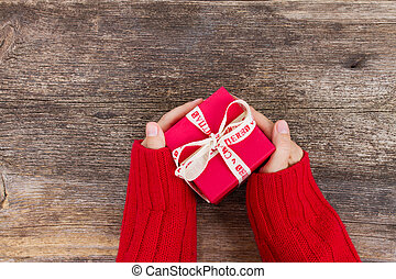 Christmas gift giving - someones hand in red knitted sweater holding red box with present