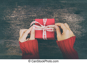 Christmas gift giving - someones hand in red knitted sweater making bow on red box with present, retro toned