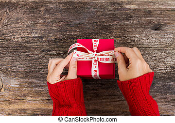 Christmas gift giving - someones hand in red knitted sweater making bow on red box with present