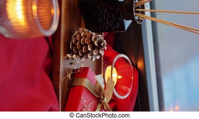 holidays, decoration and celebration concept - christmas gift, pine cone and candles on red tablecloth on window sill at home, vertical view orientation