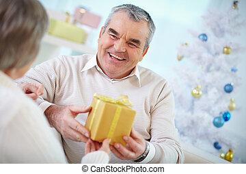 Christmas gift - Portrait of mature man giving Christmas...