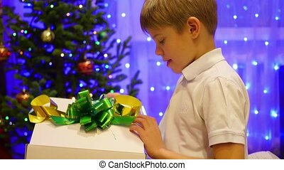 Christmas gift surprise - A kid opens a Christmas present in amazement. The glowing lights fly out of the gift box