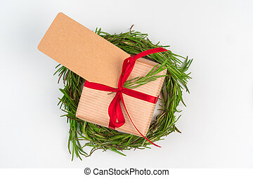 Christmas gift with red bow and greeting card on white wooden background