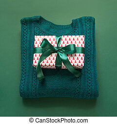 Christmas gift with ribbon, sweater on green surface. Overhead view. Holiday card. Xmas concept.