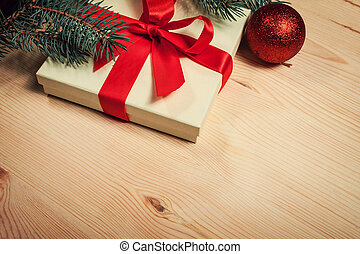 Christmas gift wrapped in red ribbon with fir twig on wooden...