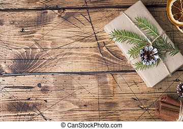 Christmas gift wrapped with decorations on a wooden table. Copy space.