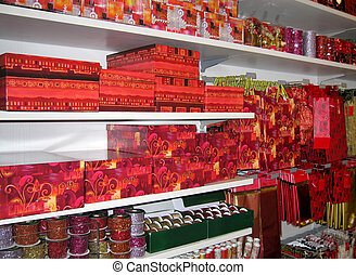In a big store, white shelves full of packaging articles and decorations for Christmas gifts. Especially red, silver and gold colors.
