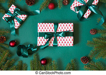 Christmas giftboxes and presents wrapping in design paper and green ribbon on green with red decor. Flat lay. Top view.