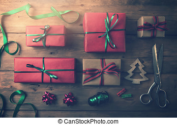 christmas gifts and wrapping accessories on wooden background. flat lay
