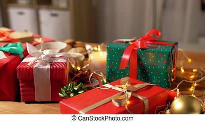 christmas gifts, candle and garland lights at home - ...