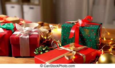 holidays, new year and christmas concept - gift boxes with name tags, candle, hot chocolate drink in mug and electric garland lights on wooden table over snow
